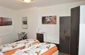 Schlafzimmer mit Doppelbett und Kleiderschrank - Ferienwohnung Palatia, Hof Rebenblüte, Weindorf Gimmeldingen, Neustadt / Weinstr. (Pfalz)